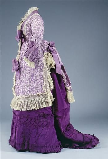 Dress, Mlle Rouault, 1875. White silk bodice with purple print and lace border. Puffed sleeves edged with ruffled purple silk faille and white lace. Rounded rectangular basque, lined front and back with lace. Purple faille skirt with pleated hem.