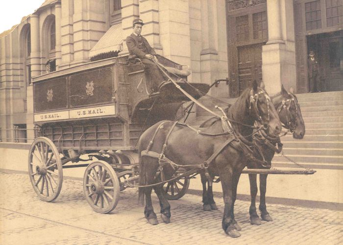 Regulation wagon, ca. 1895 - A uniformed driver sits atop a regulation wagon in Boston, Massachusetts, circa 1895. Regulation wagons were used to transport mail between Post Offices, their stations, and train stations in large cities from the 1870s to the early 1900s. The wagon pictured here was painted red, white, and blue, with gold lettering, and could haul up to 5,000 pounds of mail. By the late 1890s regulation wagons began to be phased out in favor of lighter and cheaper screen wagons.
