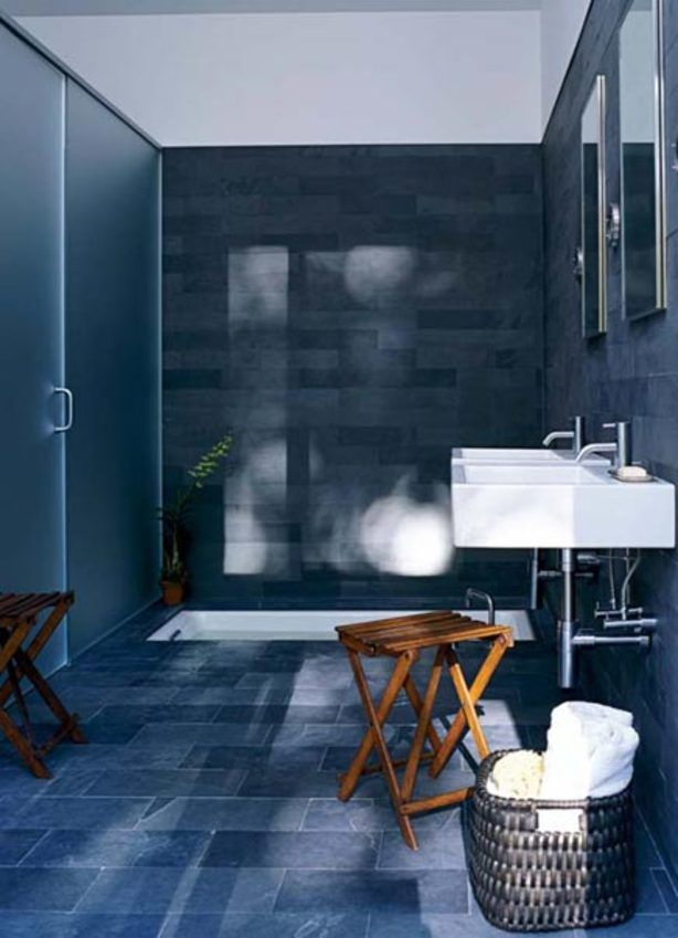Deze badkamer en eigenlijk ook het huis is ontworpen door Adam Rolston. De designer heeft gekozen om de gehele badkamer te betegelen met blauwe leisteen. De stukken op de vloer hebben een iets groter formaat, terwijl de wanden een baksteen patroon hebben met het uiterlijk van zwaar metselwerk. De badkamer is niet helemaal afgesloten. De wanden zijn betegeld tot aan de hoogte van de schuifdeur. Daarboven is het wit gelaten. inrichting-huis.com