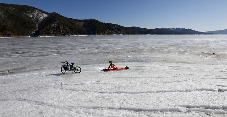 A woman enjoys the sun on the bank of the Yenisei River, with the air temperature at about 13 Celsius (55.4 degrees Fahrenheit), in the Taiga district outside Russia's Siberian city of Krasnoyarsk April 6, 2015.