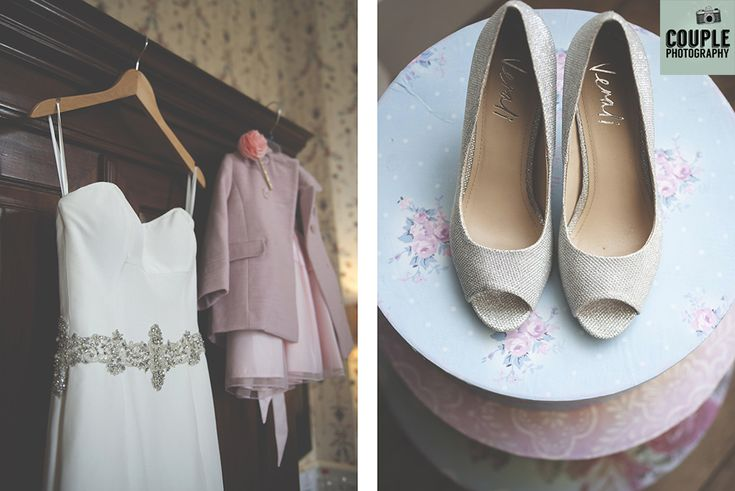 The bride's dress hanging alongside her daughters outfit. The bride's shoes in the natural window light. Weddings at Durrow Castle photographed by Couple Photography.
