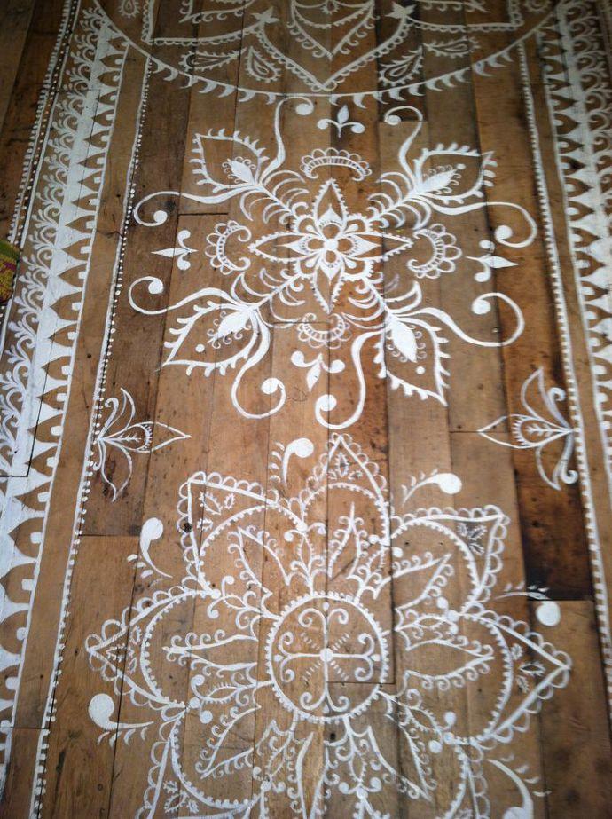 Mandalas o kolams pintados sobre suelo de madera