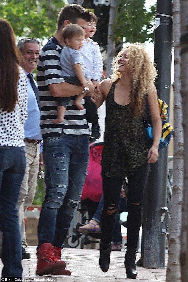 Doting parents: At one point Gerard held both Milan, two, and eight-month-old Sasha in his arms as Shakira walked alongside them, full of love for her little brood