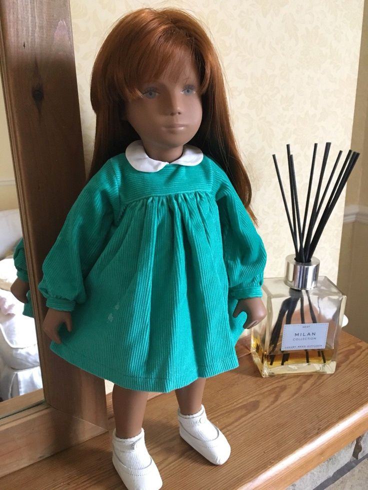 She wears a turquoise cord dress with matching pants and leather ankle strap shoes/. A re-creation of the cord outfit of the first German production and the studio doll Marianne pictured on the Lindt and Sprungli chocolate wrapper.