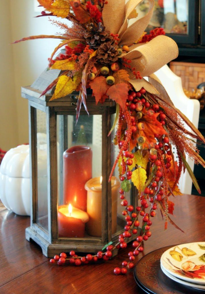 Lantern with candles, accessorized with Autumn leaves, berries and ribbon.