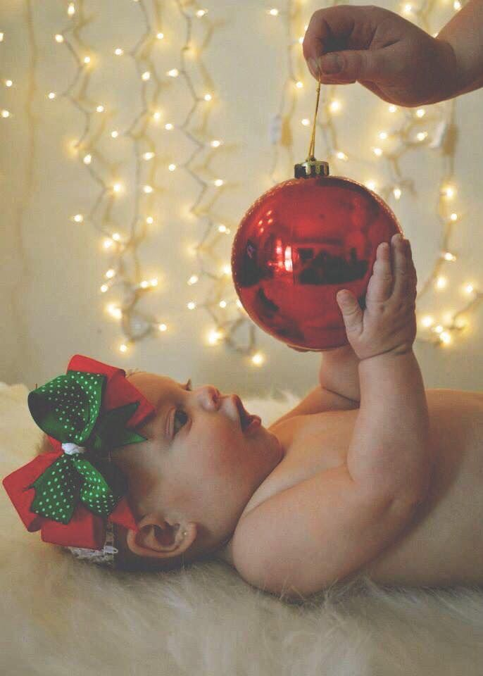 Baby, parent, and ornament. Christmas photo