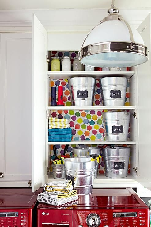 White and gray laundry room features cabinets with colorful dot wallpaper on back of shelves suspended over a glossy red washer and dryer