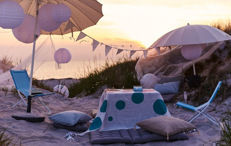 A laidback party with umbrellas, cushions and foldable chairs is set up on the beach.