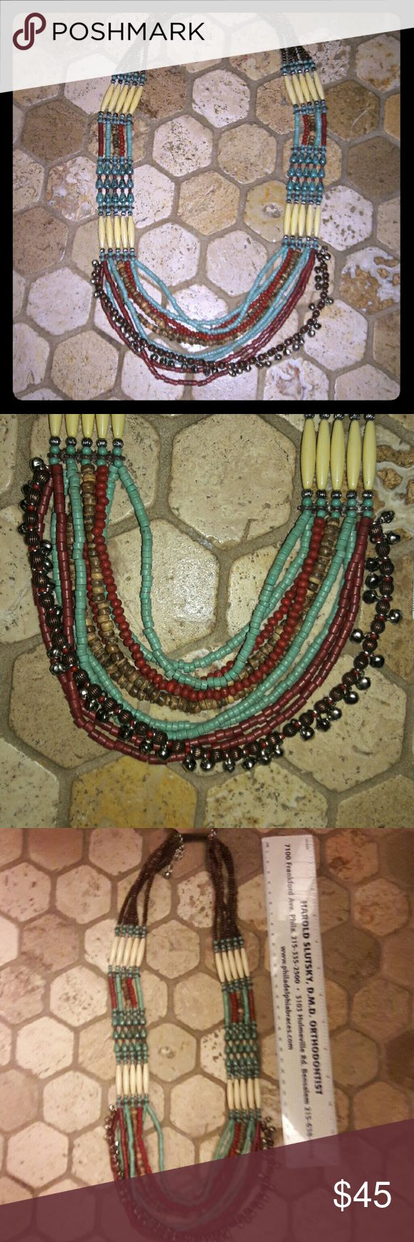 Multi-colored Five strand beaded Festival necklace A beautiful 5 stranded beaded necklace with a lobster clip closure... Turquoise and Bone white ivory and maroon in color... has dangling beaded Bell like chain on the last round as shown in pics... Any questions please ask... Great for festivals... Or any occasion you could dress it up or down Treska Jewelry Necklaces