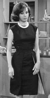 Laura Petrie wears her little black dress and pearls in her midcentury kitchen.