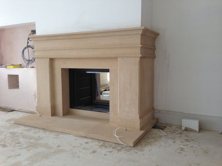 An Asymmetrical Stone Fireplace Around A Stuv Stove