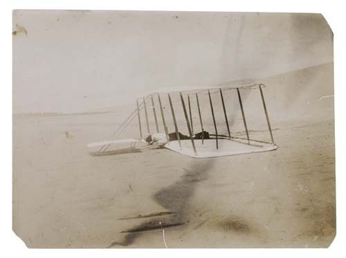 """Wright Brothers, with Orville in the 'Cockpit' """"This flyer, seen at Kitty Hawk in 1901, was unsuccessful as a manned kite but was used as a glider."""", 1901 / src: Swann Galleries"""