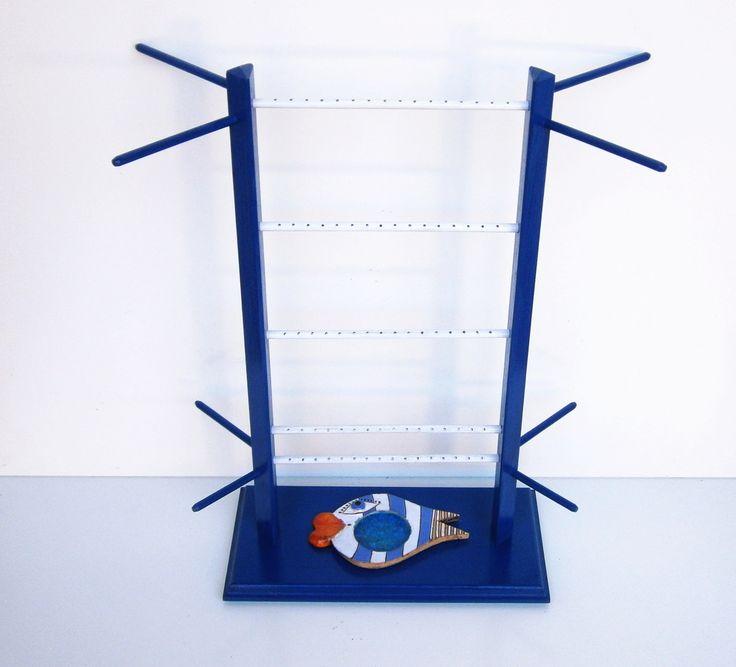 Dřevěný stojan na šperky modrý s rybou Dřevěný stojan na šperky s keramickou mističkou (Fler, ALLKA, rybička s prohlubní, která je na dně vyplněna roztaveným barevným sklem), je vyrobený ze smrkového dřeva. (vršek) a středně tvrdé dřevovláknité deksy (obdélníková základna) Mistička ve tvaru ryby o rozměrech 13cm x 8,5 cm slouží pro ukládání prstýnků či ...