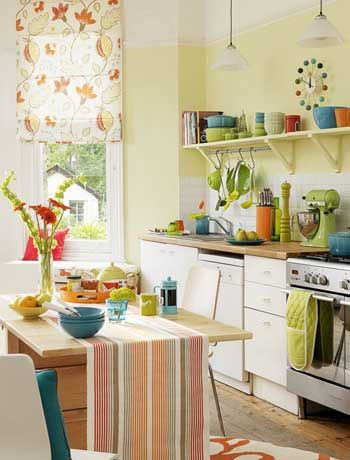 Small kitchen.  Yellow walls, bright bowls, open shelves, bright stripe table runner.  Yellow, orange, blue and red