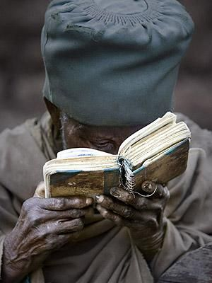 Pilgrim - Lalibela, Ethiopia  A pilgrim reads from a well-worn prayer book near the church at Bet Giorgis. The most popular prayers among the Christian Orthodox of Ethiopia are the Psalms of David. Ethiopians are the oldest followers of Christianity on the continent of Africa.
