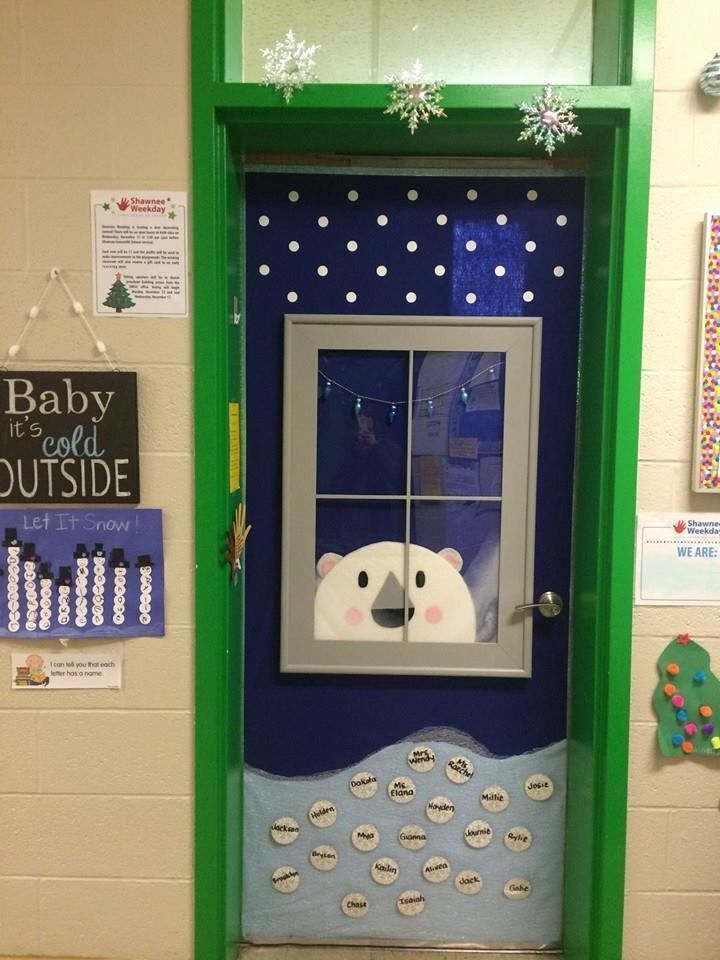 "This is my preschool classroom door.  My hubby built the frame of the window and put plexiglas for the window.  He cut the bear out of High R sheeting and I covered the bear with batting.  I used felt shapes as the elements of the bear.  The light and dark blue are felt.  The bottom ""snow"" is tulle."