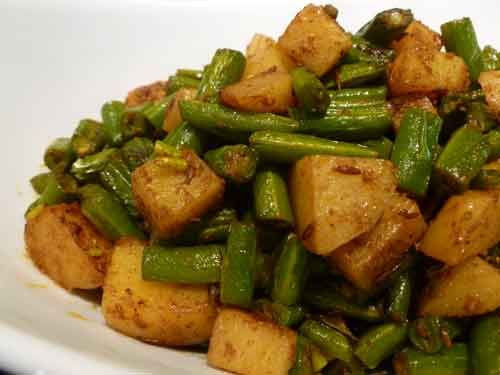 Green beans with potatoes. Leave out the garam masala. And make everything in the pressure cooker. After adding the beans and potatoes, add 1.5 cups of water and pressure cook.