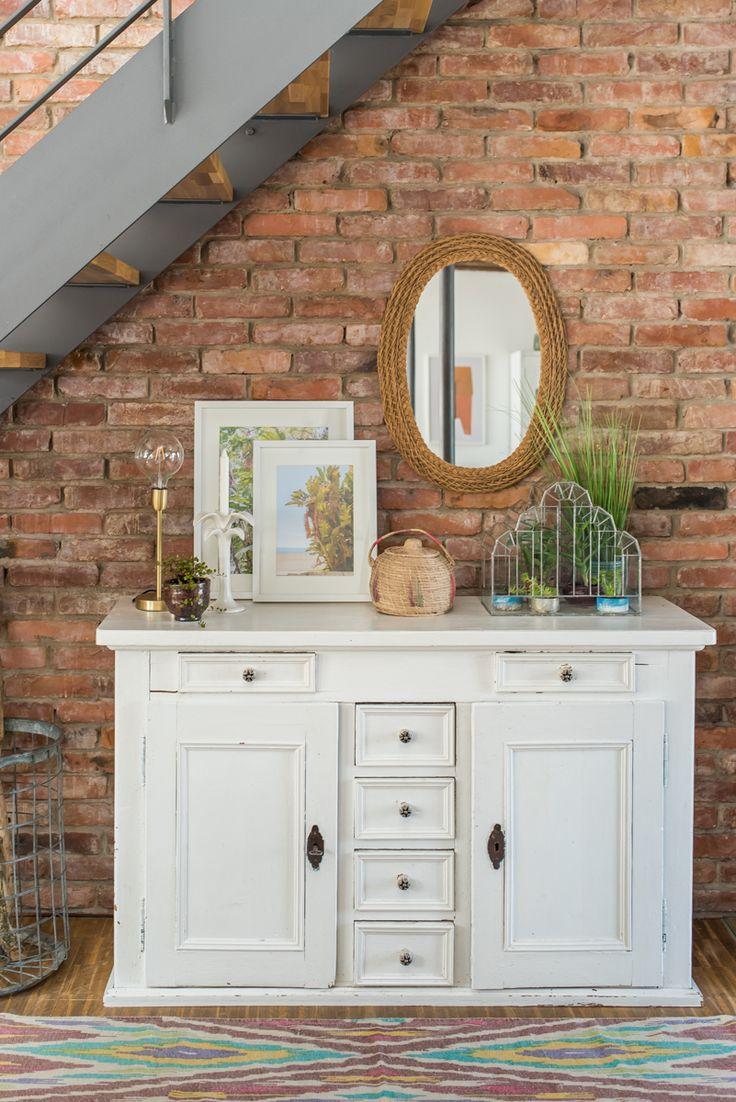 Dekoideen für das sideboard im wohnzimmer mit pflanzen und sukkulenten vor einer backsteinwand im sommerlichen boho