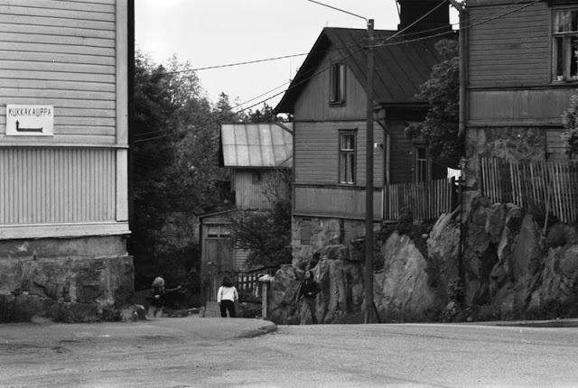Nuorisoa Pasilankadulla Länsi-Pasilassa. Keskellä Pasilankatu 18 ja 20, oikealla Pasilankatu 22:n talon kulma. Vasemmalla olevan puutalon seinällä kukkakaupan kyltti. 1970