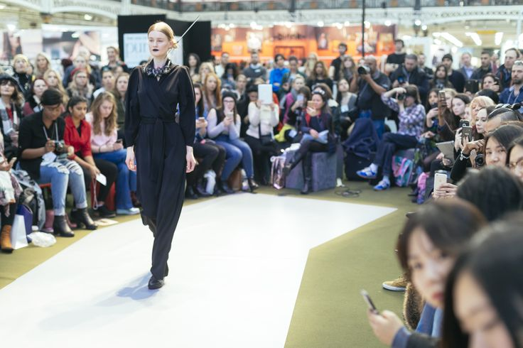 Elegantly walking back down the runway, one model showcases a black jumpsuit and statement necklace, after having been photographed. The crowds watch in awe, trying to capture the moment on their mobile phones and camera. This catwalk took place at the main stage