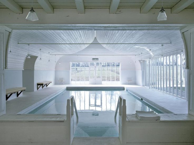 The pale blue walls of this pool house echo the calming pool water, making the space feel relaxed and tranquil. The ceiling is shaped like the hull of a ship, adding distinct character to the room.