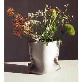 Plünnen ist eine handgefertigte Vase aus Textilbeton. Die Vase hat außen eine weiche textile Oberfläche und innen eine Schicht PVC. Zwischen diesen beiden Schichten ist Beton. Dadurch sieht die Vase zwar nach Textil aus, ist aber doch hart wie Beton. Die Nähte sind mit Silikon abgedichtet, sodass die Vase Wasserdicht ist.Die Auswahlfarbe bezieht sich auf die Farbe der Nähte.Die Maße: ca. 17 cm x 15 cm x 10 cm