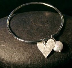 Hand crafted in our in house studio, this stylish silver bangle comes strung with a solid silver heart and white pearl charms.  As is the nature of semi-precious stones, the stones on each bangle may vary from the picture shown.