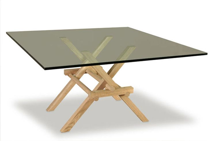 LEONARDO, table made of solid oak and glass top. The joints of the legs, without metal joints, is inspired by the construction of movable bridges of Leonardo da Vici. Design Marco Ferreri