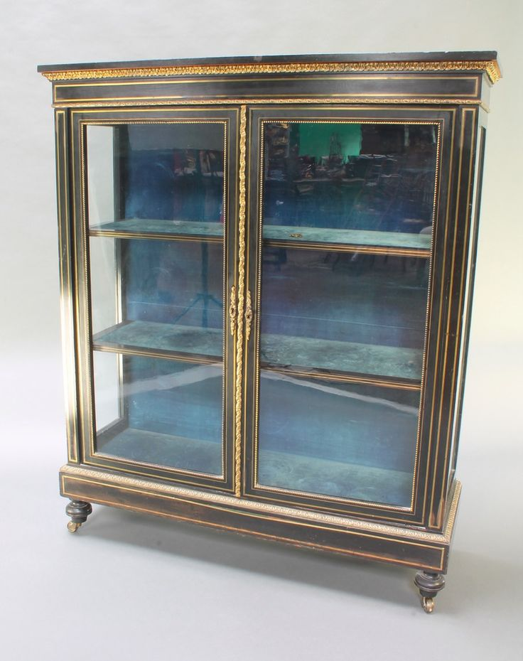 """Lot 900, A Victorian ebonised display cabinet with gilt metal mounts and inlay, fitted 3 shelves, raised on turned feet with brass casters 48""""h x 41""""w x 14""""d EST £200-300"""