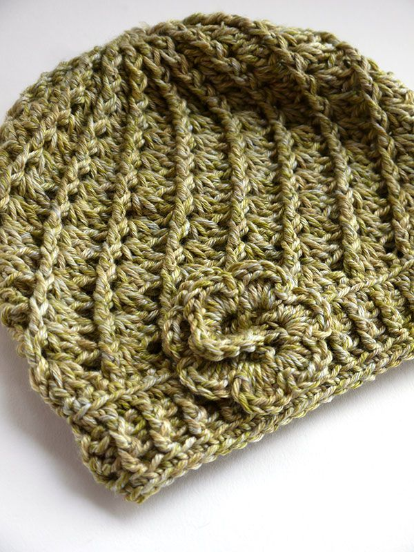 CROCHETED HAT | This easy textured beanie crochets quickly in all double crochet stitches, using front and back post crochet techniques to create ridges that spiral up the body of the hat. Crocheted in a cotton blend yarn, like Berroco Floret, this cute hat is light, airy, and perfect for spring. Topped with a crocheted flower or a large button you'll receive lots of compliments on your new accessory.