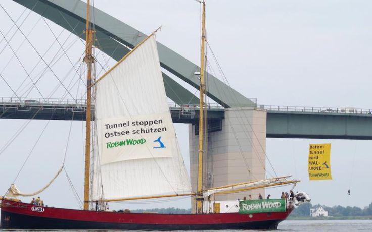 """Aus Protest gegen die geplante Untertunnelung des Fehmarnbelts haben sich ROBIN WOOD-Aktivisten von der Fehmarnsundbrücke abgeseilt.Sie spannten dort ein Transparent mit der Aufschrift """"Beton-Tunnel wird WAL-URNE"""". Begleitet wird die Aktion vom Traditionssegler LOVIS,der ein Banner mit dem Slogan """"Tunnel stoppen–Ostsee schützen""""hisste.Auch VertreterInnen des Bündnisses Beltretter sind vor Ort.R.W. fordert einen Verzicht auf den Bau einer festen Fehmarnbeltquerung/Beibehaltung der…"""