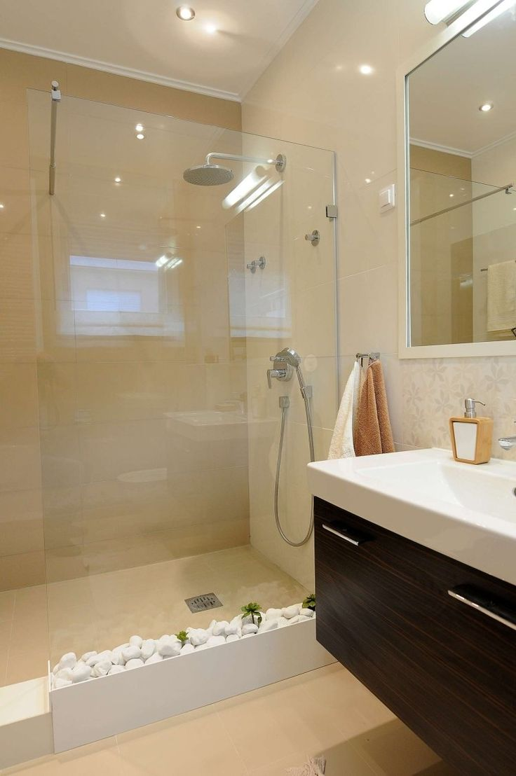 petite salle de bains avec un carrelage beige, paroi de douche transparente et galets décoratifs