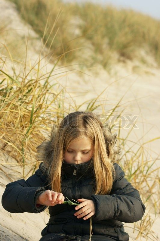 Autumn girl on beach playing with grass straw stock photo on Colourbox