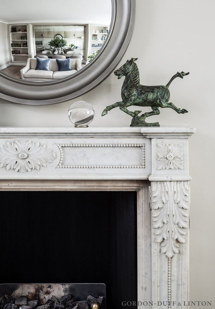 Detail of Spanish 1900s fireplace in living room. Round convex mirror and ornamental horse.