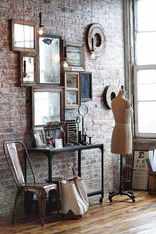 decoração vintage / ainsustrial com parede de tijolos a vista e quadros com molduras antigas pendurados na parede sem espaços entre as peças