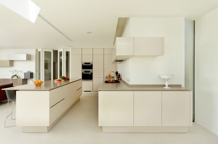 This sleek handleless kitchen featuring Miele appliances and a unique layout. The result is a flowing kitchen space with distinct zones, and a great island seating area for entertaining and every day family use