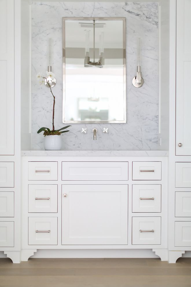 white bathroom features a white washstand paired with a marble countertop and backsplash lined with a modern faucet and a chrome mirror