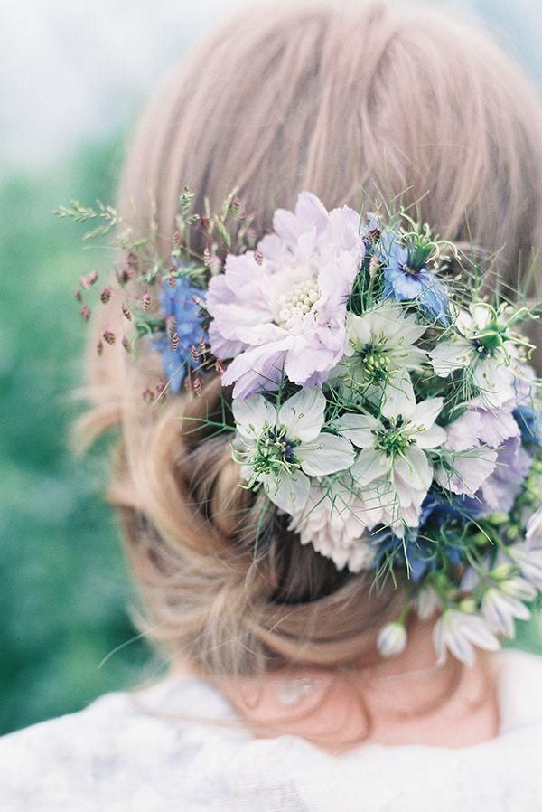 A softly pulled-back braided bun with a small bouquet of light flowers is perfect for a spring #TOMSwedding.