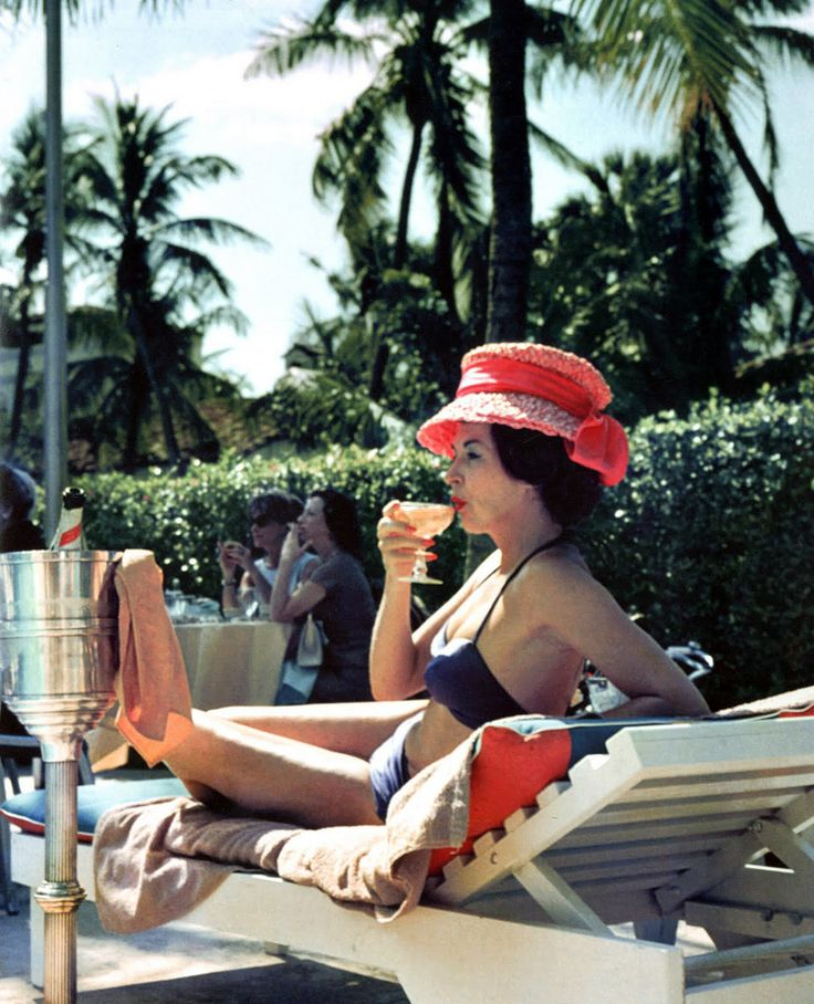 A woman watching a poolside fashion show at the Colony Hotel, Palm Beach, Florida, 1961.