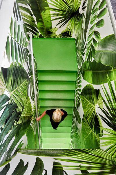 L'escalier vert Greenery se voit encerclée par un papier peint aux imprimé feuille pour une ambiance tropicale