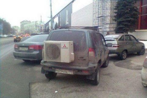 An einem Auto wurde eine externe Klimaanlage angebaut. Diese ist sehr groß und befindet sich an der Heckklappe des Wagens.