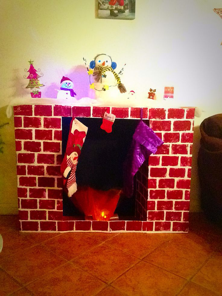 DIY fireplace. Made with 4 white tri-fold presentation boards cut and folded to shape.  You could also stack cardboard boxes then cover with paper to make them one even color. I then used a sponge and acrylic paint to carefully make a bricklay pattern.  Personalize with fake candles inside with red and orange tulle over the LED tea lights to give look of fire