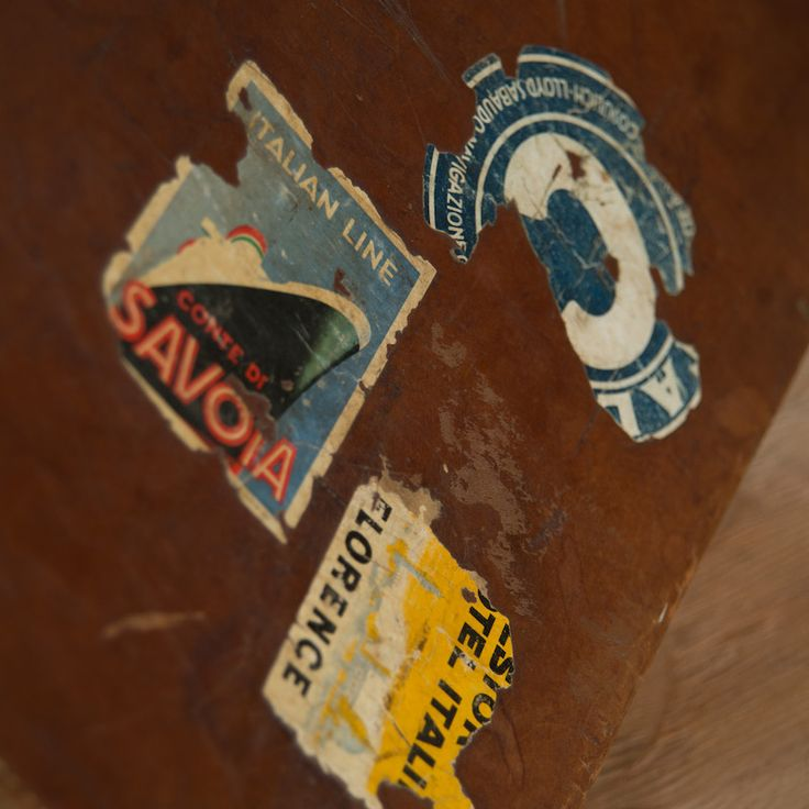 Ascott Leather Suitcase at Found Vintage Rentals. Distressed brown leather suitcase with travel stickers.