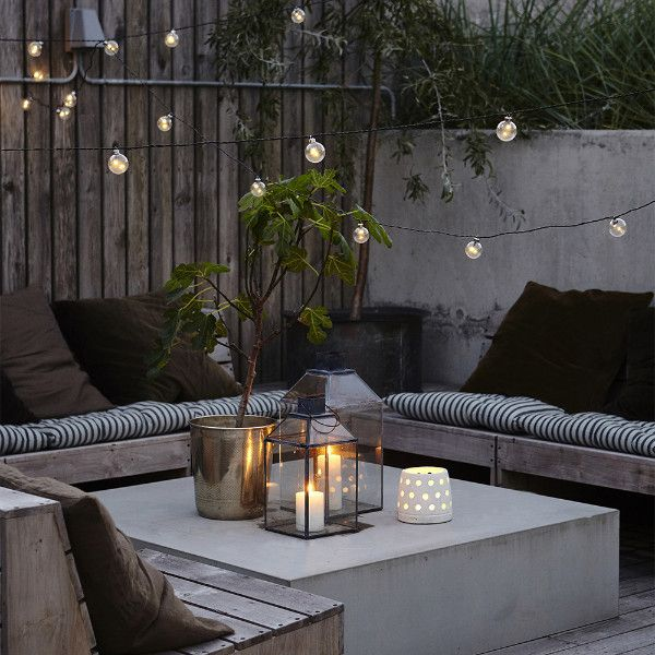 Stylish festoon lights from Danish company House Doctor. Add these stylish LED lights to a yard or back garden for instant feature lighting. The modern concrete and wood really works in this photo. Glass votives, tealights, metal plantpots and fabrics all soften the look. Making it really easy to recreate in your home.