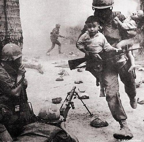 Un infante de marina EE.UU. en Vietnam lleva a los niños fuera de peligro ... de 1960