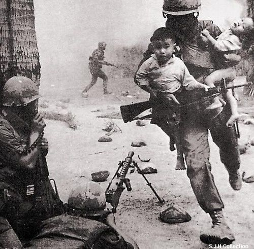 A Marine in Vietnam carries children out of danger.