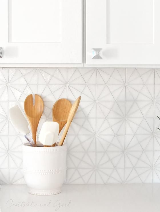 Gorgeous kitchen features white cabinets paired with Caesarstone Pure White Quartz countertops and a white iridescent hexagon tile backsplash, Oceanside Glass Tessera Kaleidoscope Tiles.