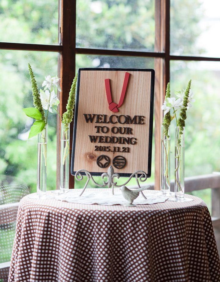 和風の会場や料亭で和の結婚式をするなら、ウエルカムボードも素材からこだわってみては。杉の板に「縁を結ぶ」という意味を込めて結び目のモチーフをプラス、ふたりの名前ではなく家紋を入れて一層「和」を引き立てて♪