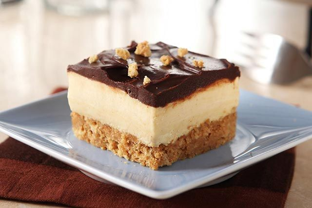 A peanut butter cookie crust is topped with layers of creamy peanut butter and chocolate—elevating these dessert squares from a candy store favourite to an elegant delight.