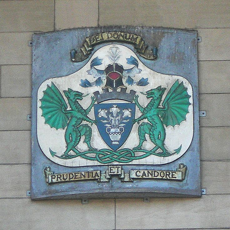 """Dundee arms and mottos : the azure shield which shows a pot with three lilies is surmounted by a coronet and a casket also with lilies and it is supported by two green dragons. The oldest latin motto reads """"Dei Donum""""  (""""God's Gift"""") and the more recent one """"Prudentia et Candore"""" (with thought and purity)"""